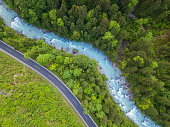 The whitewater river Steyr next to a paved road. The water is still blue from the melting snow in the montains in springtime. Location: next to the small ski resort Hinterstoder in the 'Totes Gebirge' area in Upper Austria.