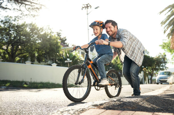 wer könnte das besser als mit papa fahren lernen - kinderfahrrad stock-fotos und bilder