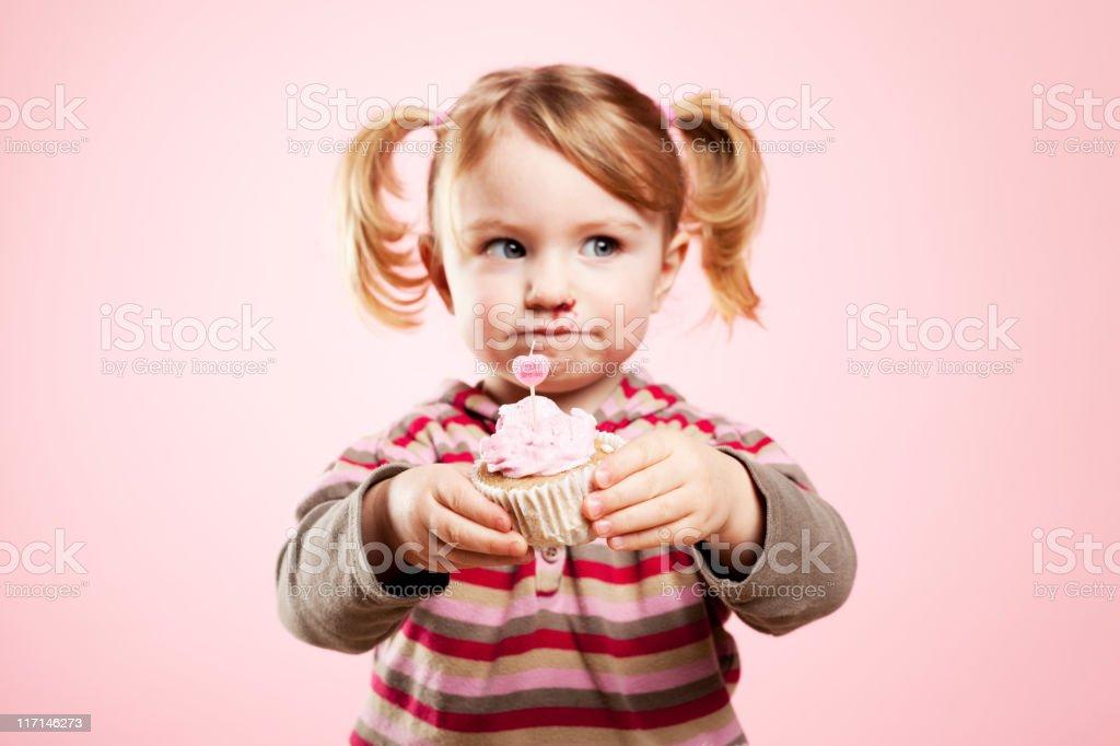 Who bite the birthday cake? Cute girl holding cupcake royalty-free stock photo