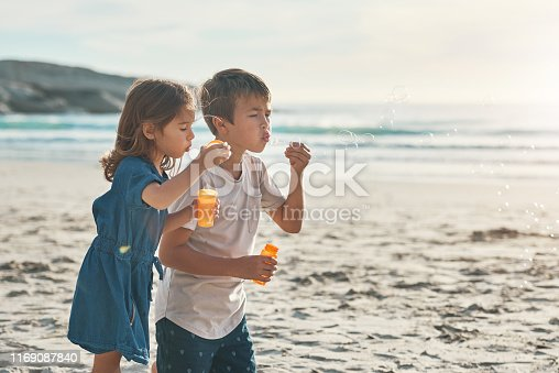 Cropped shot of two young siblings standing together and blowing bubbles during a relaxing day on the beach