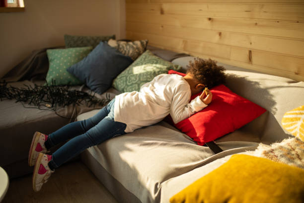 Who is hiding there ? Baby girl lying on sofa with head on pillows and holding cookie head in the sand stock pictures, royalty-free photos & images