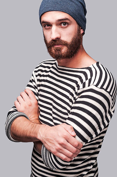 Who is the man? Confident young bearded man in striped clothing keeping arms crossed and looking at camera while standing against grey background sailor suit stock pictures, royalty-free photos & images