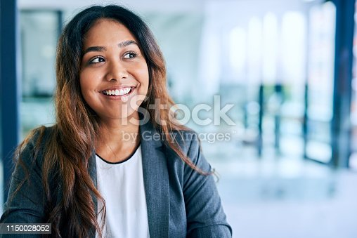Shot of a young businesswoman looking thoughtful while working in a modern office