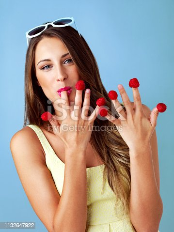 Studio shot of a woman eating raspberries off her fingertips against a blue background