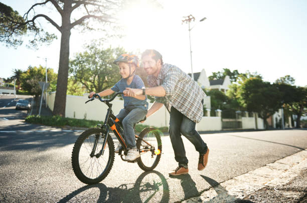 Who needs training wheels when you've got dad? stock photo