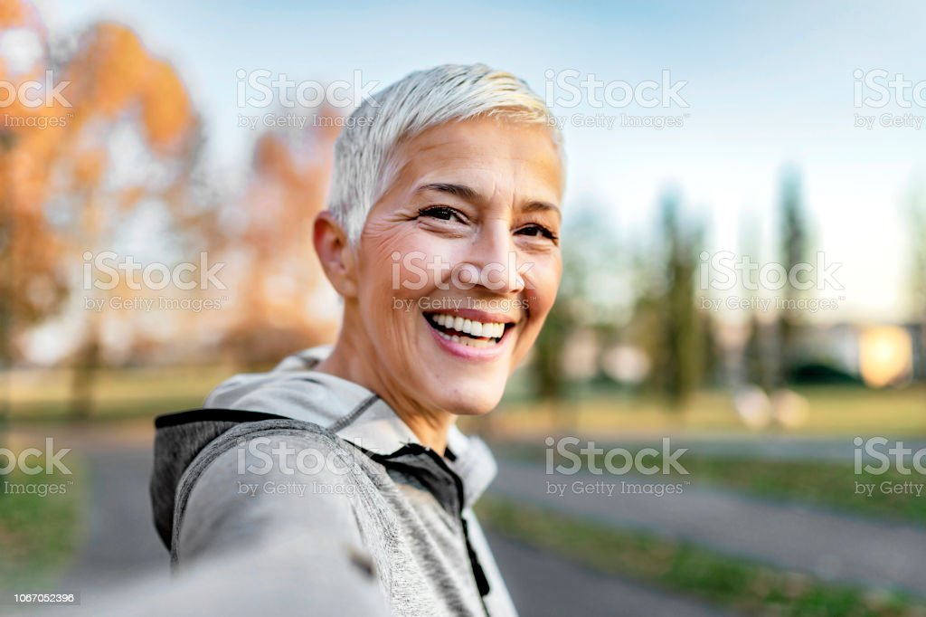 Who said selfies are just for the youth? Close Up Portrait of Happy Cheerful Delightful Charming Beautiful Mature Lady Granny Grandma Taking a Selfie on Vacation. Selfie Portrait of Happy Senior Woman With Short Gray Hair Outdoor. Sporty Senior Woman Taking Selfie in the Park After Workout. 50-59 Years Stock Photo