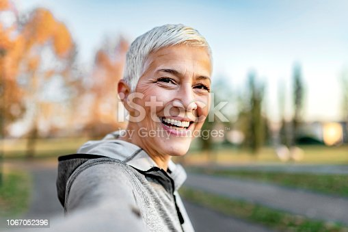 Close Up Portrait of Happy Cheerful Delightful Charming Beautiful Mature Lady Granny Grandma Taking a Selfie on Vacation. Selfie Portrait of Happy Senior Woman With Short Gray Hair Outdoor. Sporty Senior Woman Taking Selfie in the Park After Workout.