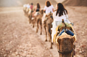 Rearview shot of a group of women riding on camels in a desert