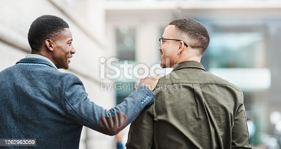 Rearview shot of two young businessmen walking through the city together