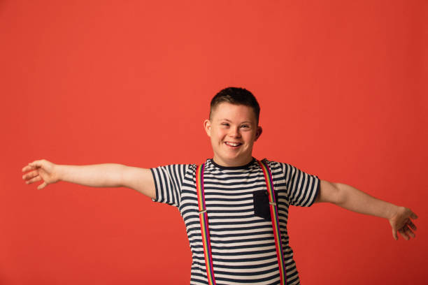 Who Wants A Hug? A teenage Down syndrome boy standing in a studio with his arms stretched out, looking happy and positive. suspenders stock pictures, royalty-free photos & images