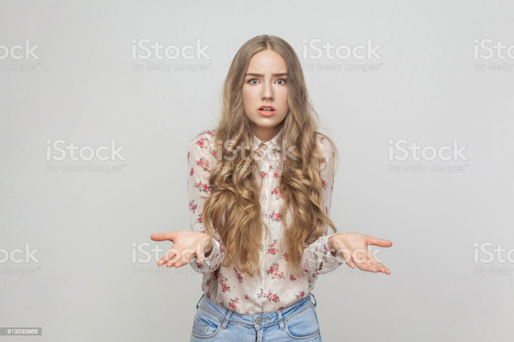 Who? Why my? Confused girl looking at camera with puzzled look stock photo