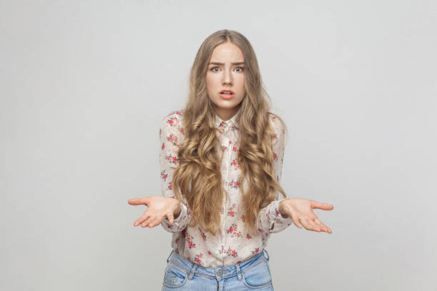 Who? Why my? Confused girl looking at camera with puzzled look Who? Why my? Confused girl looking at camera with puzzled look. Studio shot, gray background nerd hairstyles for girls stock pictures, royalty-free photos & images