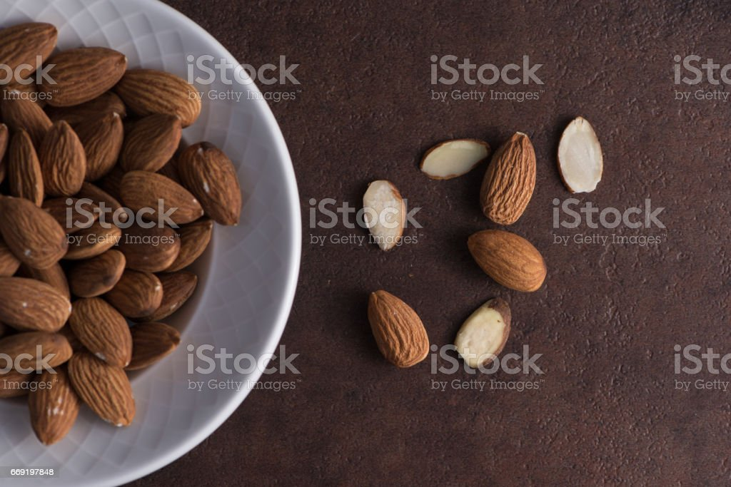 Whole almonds in white bowl rusted surface sliced almonds