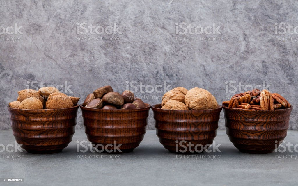 Whole almonds,whole walnuts ,whole hazelnut and pecan nuts in wooden bowl setup with stone background.  Selective focus depth of field. stock photo