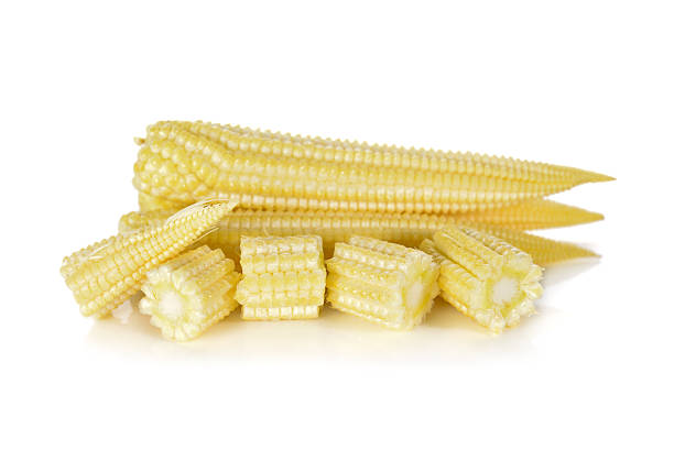 whole and cut baby corn on white background stock photo