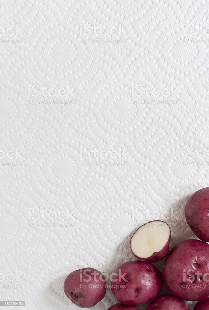 Whole and Cut Red Potatoes on a Paper Towel royalty-free stock photo