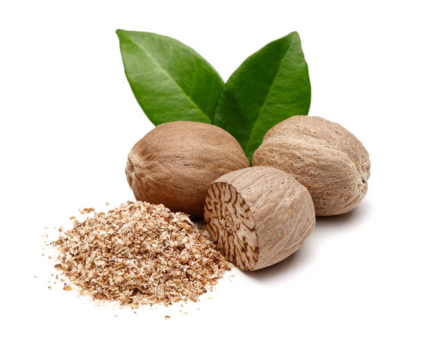 Whole and grated nutmeg with leaves isolated Whole and grated nutmeg with leaves isolated on white background nutmeg stock pictures, royalty-free photos & images