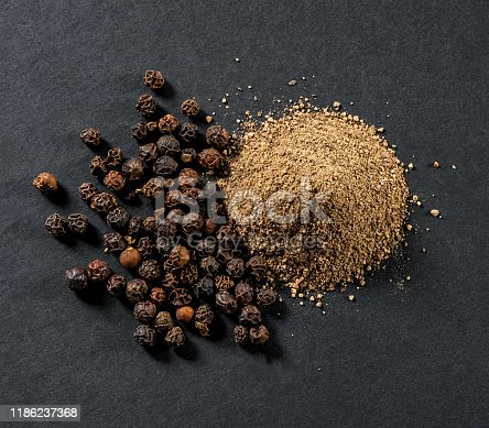 whole and ground black allspice peppercorns close-up on gray background view from above