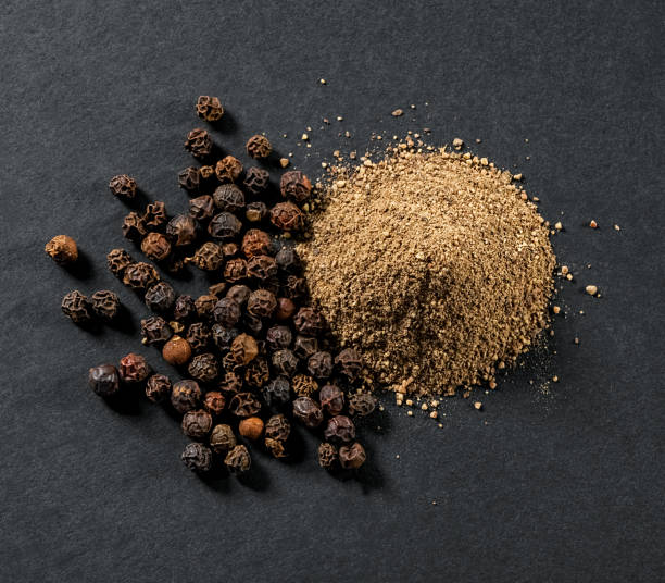 whole and ground black allspice peppercorns close-up on gray background whole and ground black allspice peppercorns close-up on gray background view from above allspice stock pictures, royalty-free photos & images