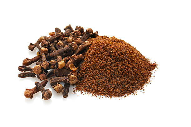 Whole and Ground Cloves, Isolated on White Grouping of whole dried cloves and ground cloves.  Shot on white background with natural reflections.Shot with Nikon D3x and shift lens. burwellphotography stock pictures, royalty-free photos & images