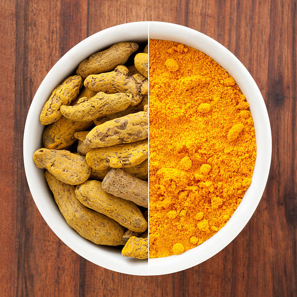 Whole and ground turmeric root composition stock photo