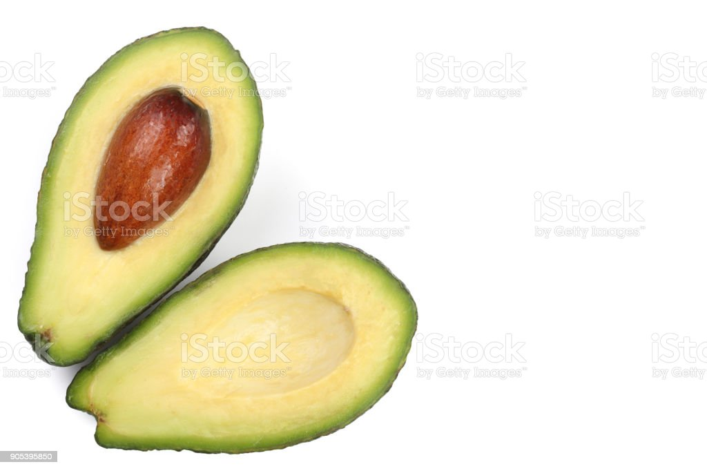 whole and half avocado isolated on white background close-up with copy space for your text. Top view. Flat lay pattern stock photo