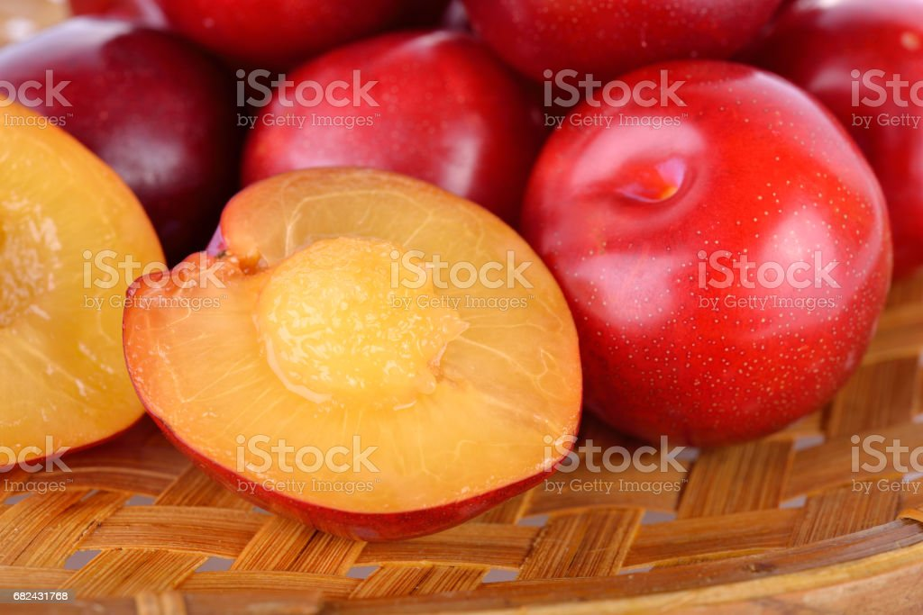 whole and half cut fresh gulf ruby plum in the bamboo basket royalty-free stock photo