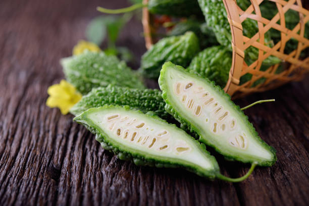 whole and half cut raw bitter gourd on wooden background stock photo