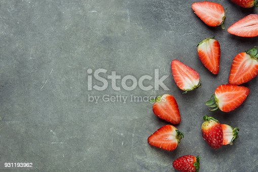 istock Whole and Halved Ripe Organic Strawberries Scattered on Black Stone Background Arranged in Border. Summer Vitamins Healthy Lifestyle Beauty. Creative Minimalist Image with Copy Space 931193962