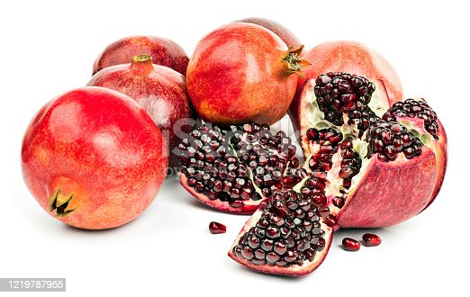 Several ripe whole and peeled pomegranate fruits and pomegranate grains isolated on white background.