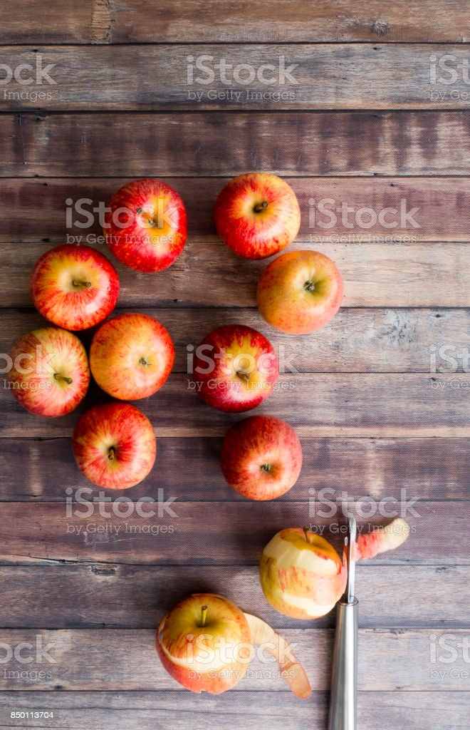 Whole and Peeled Red Apples on Brown Wood Background stock photo