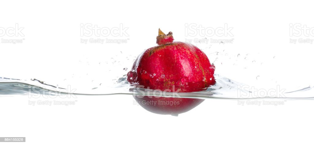 Whole and ripe garnet in water. Isolated horizontal picture on white background royalty-free stock photo