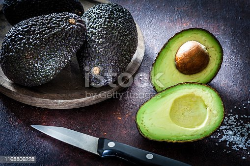 Top view of healthy ripe organic whole and sliced avocados shot on dark abstract table. Predominant colors are green and brown. Low key DSRL studio photo taken with Canon EOS 5D Mk II and Canon EF 100mm f/2.8L Macro IS USM.