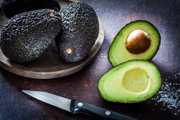Ganze und in Scheiben geschnittene Avocados Stillleben – Foto