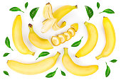 whole and sliced bananas decorated with green leaves isolated on white background. Top view. Flat lay.