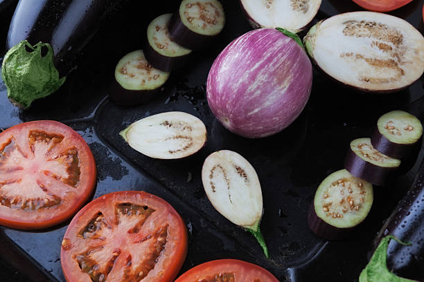 whole and sliced eggplants and tomatoes on baking tray closeup - black beauty photos et images de collection