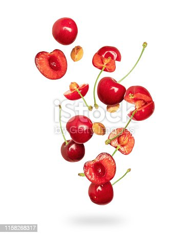 istock Whole and sliced fresh cherries in the air on a white background 1158268317