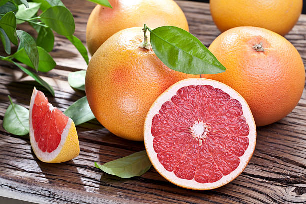 Whole and sliced grapefruits on a wet wooden table stock photo