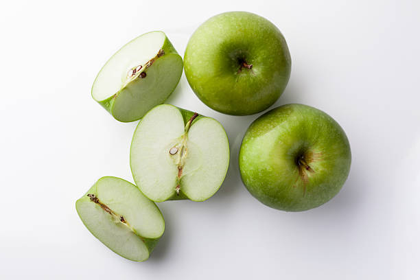 Whole and sliced green apples from above on white Two whole green apples and one sliced on white background directly from above granny smith apple stock pictures, royalty-free photos & images