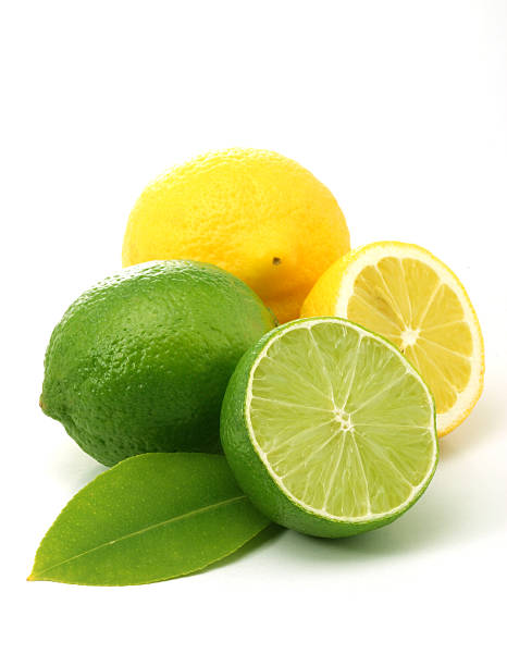 Whole and sliced lemons and limes on a white background stock photo