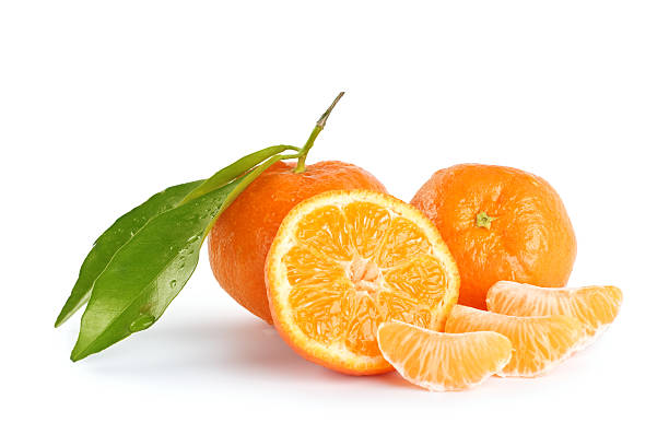 Whole and sliced mandarins on a white background Fresh orange mandarines, pieces, leaves and cross section against white background tangerine stock pictures, royalty-free photos & images