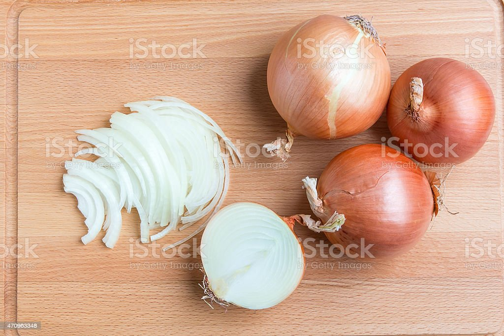 Whole and sliced onions on wooden cutting  board stock photo