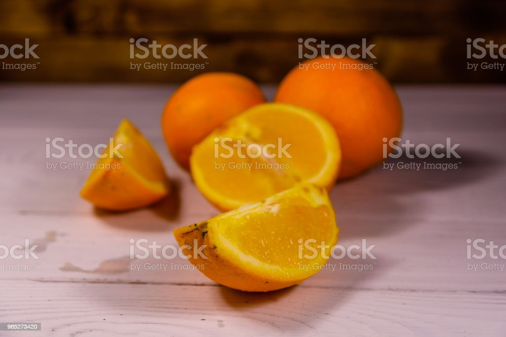 Whole and sliced oranges on a wooden table zbiór zdjęć royalty-free
