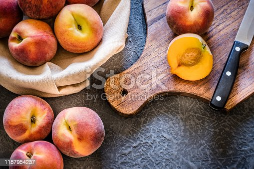Top view of a sliced peach on a wooden cutting board alongside a kitchen knife and a heap of whole peaches on dark gray textured background. Peaches are at the top of the image so there is a useful copy space at the lower right side on the background. Low key DSLR photo taken with Canon EOS 6D Mark II and Canon EF 24-105 mm f/4L