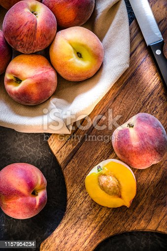Top view of a sliced peach on a wooden cutting board alongside a kitchen knife and a heap of whole peaches. Low key DSLR photo taken with Canon EOS 6D Mark II and Canon EF 24-105 mm f/4L
