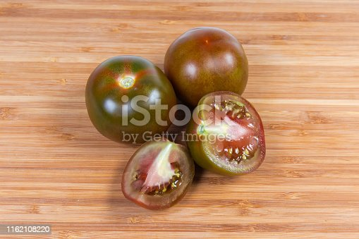 Two whole and one sliced ripe reddish brown tomatoes kumato on the wooden cutting board
