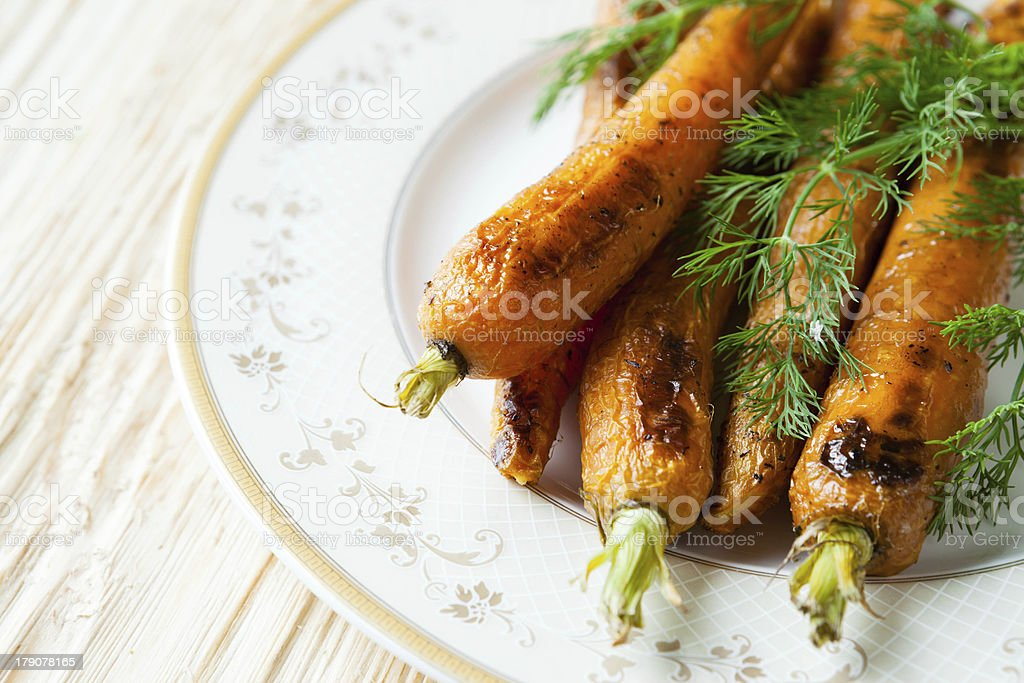 whole baked carrots on a plate royalty-free stock photo