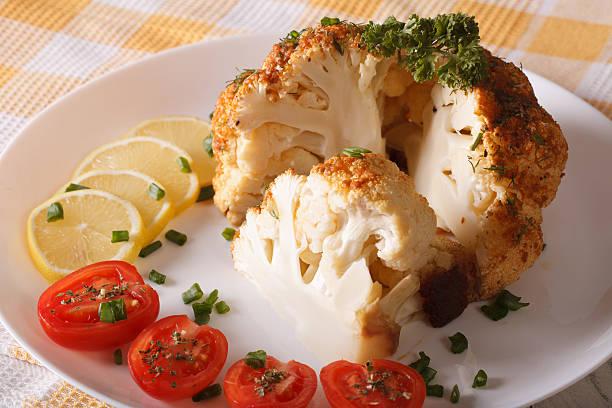 whole baked cauliflower and fresh tomatoes and lemons close-up - gebackener blumenkohl stock-fotos und bilder
