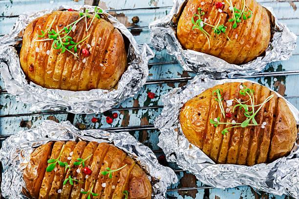 ganzer, gebackener kartoffel in metallic - alufolie backofen stock-fotos und bilder