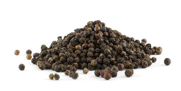 PILE OF SPICES - whole black peppercorns stock photo